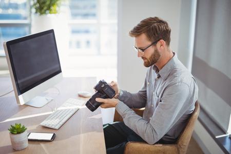 Executive looking at digital camera at desk in office