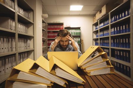 Worried businessman looking at laptop in file storage room