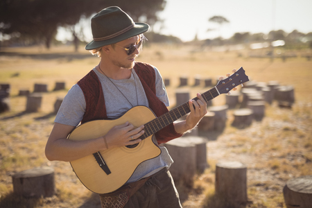 Young man playing guitar while standing on field at forest