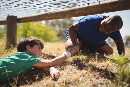 Photo pour Boy helping his friend during obstacle course in boot camp - image libre de droit