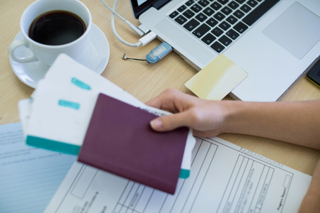 Close-up of female executive holding tickets and passport at her desk in office