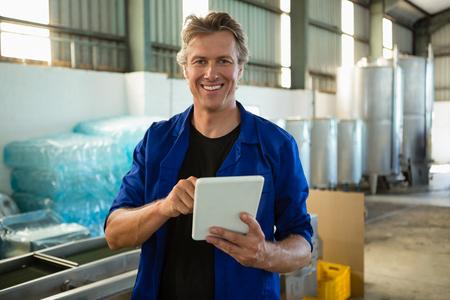 Portrait of smiling worker using digital tablet in factory