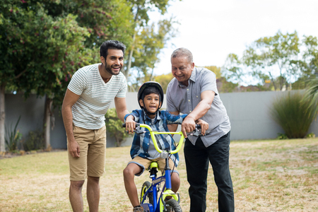Father and grandfather assisting boy for riding bicycle while standing in yard