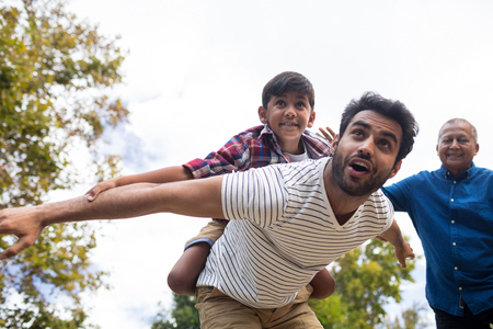 Smiling grandfather looking at man giving piggy backing to son with arms oustretched in yard