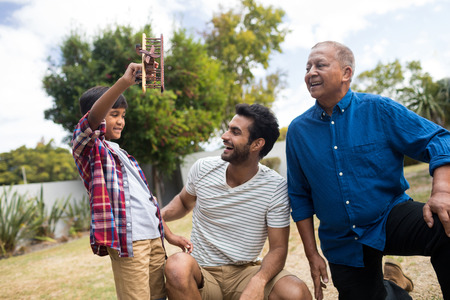 Boy showing toy airplane to father crouching by senior man in yard