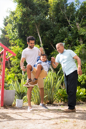 Playful father and grandfather with boy at park during sunny day