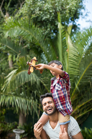 Happy father carrying playful son while standing in yard