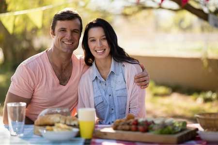 Portrait of happy couple sitting together with arm around in park