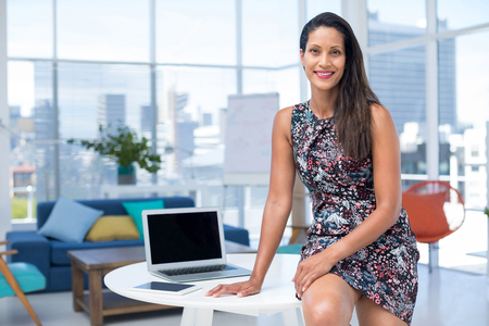 Photo for Portrait of female executive sitting on desk in the office - Royalty Free Image