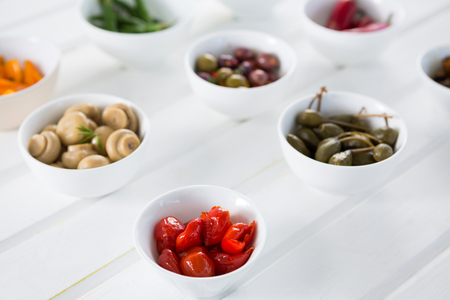 Marinated olives and vegetables arranged on white background