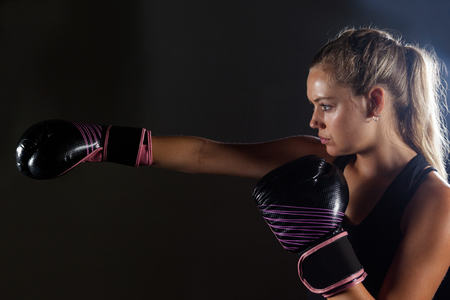 Determined woman practicing boxing in fitness studio