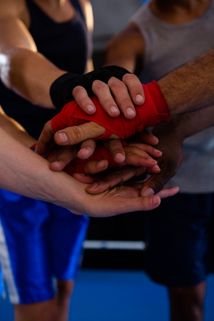 Close-up of boxers stacking hands in boxing ring