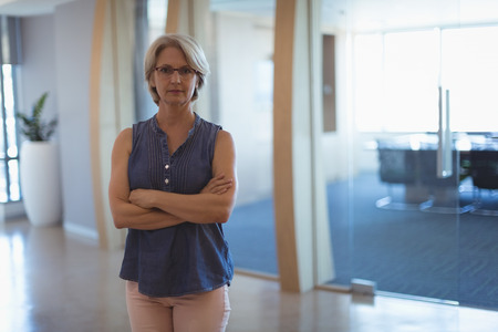Portrait of mature businesswoman with arms crossed standing in office