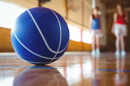 Close up of blue basketball on floor with female players in background