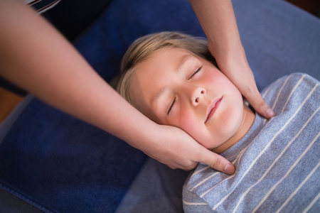 Boy lying with eyes closed receiving neck massage from female therapist at hospital ward