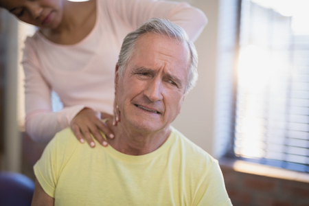 Senior male patient frowning while receiving neck massage from therapist at hospital ward