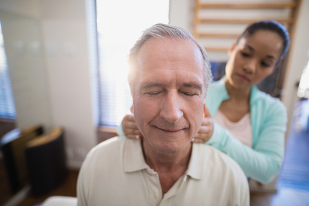 Senior male patient with eyes closed receiving neck massage from female therapist at hospital ward