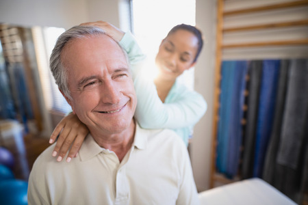 Smiling senior male patient receiving neck massage from female therapist at hospital ward