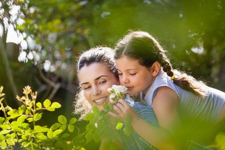 Foto de Girl smelling white roses while enjoying piggyback ride on mother in yard during sunny day - Imagen libre de derechos