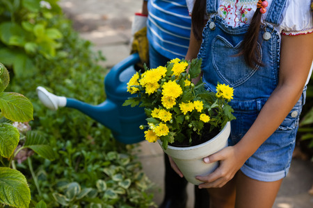 Midsection of senior woman and granddaughter holding watering can and yellow flower pot at backyard