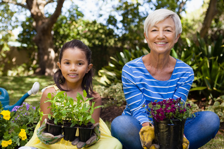 Portrait of smiling girl and granddaughter sitting while holding plants at backyard