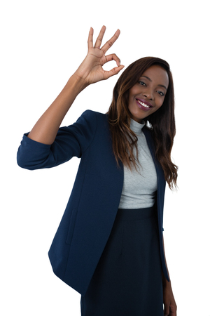 Portrait of smiling businesswoman showing ok sign while standing against white background