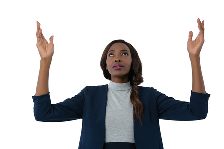 Close up of businesswoman looking up while gesturing against white background