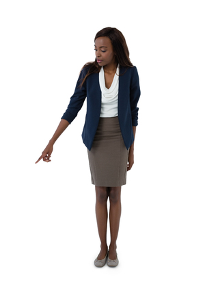 Full length of businesswoman pointing while standing against white background
