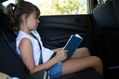 Attentive teenage girl reading book in the back seat of car