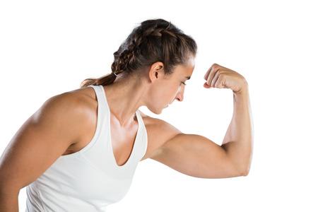 Foto de Female athlete flexing muscles against white background - Imagen libre de derechos