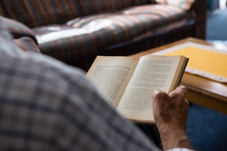 Cropped hand of senior man reading book in nursing home