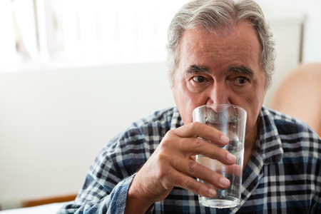Senior man drinking water while sitting in nursing home