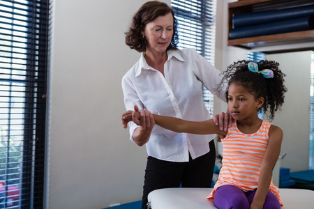 Physiotherapist giving hand massage to a girl in clinic