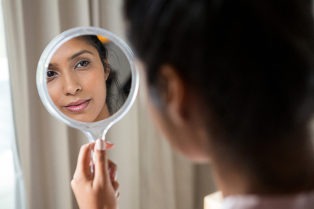 Photo pour Young woman reflecting on hand mirror at home - image libre de droit