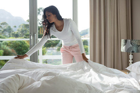 Foto per Young woman making bed at home - Immagine Royalty Free