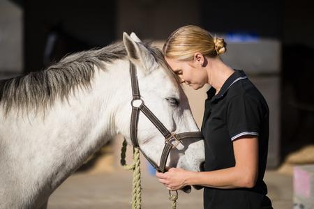 Photo pour Side view of female jockey loving horse at barn - image libre de droit