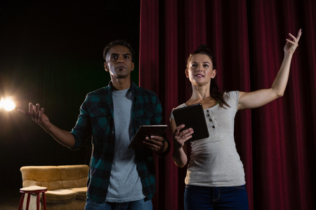 Actors rehearsing on stage while using digital tablet in theatre