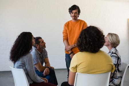 Foto de Man standing by fiends sitting on chair in art class - Imagen libre de derechos