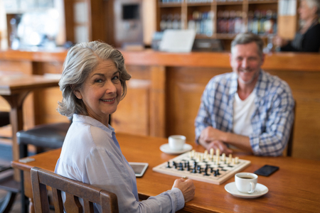 Happy man and woman looking at camera while playing chess in bar