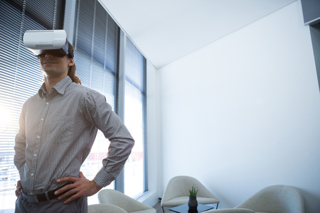 Male executive using virtual reality headset in waiting area of office