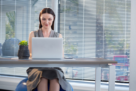 Female executive sitting on exercise ball while working at desk in office