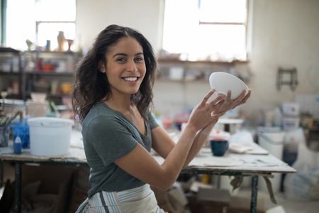 Photo for Smiling pretty potter examining her creation in the pottery workshop - Royalty Free Image