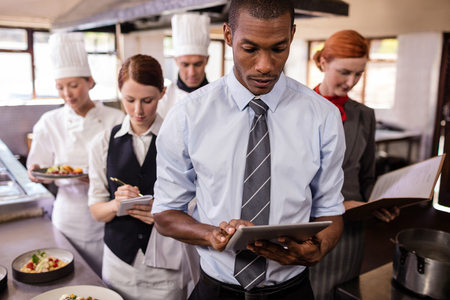 Photo pour Group of hotel staffs working in kitchen at hotel - image libre de droit