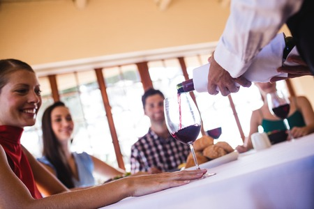 Photo pour Waitress pouring red wine in wine glass on table in restaurant - image libre de droit