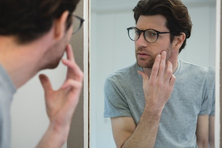 Photo pour Man looking his face in mirror at home - image libre de droit