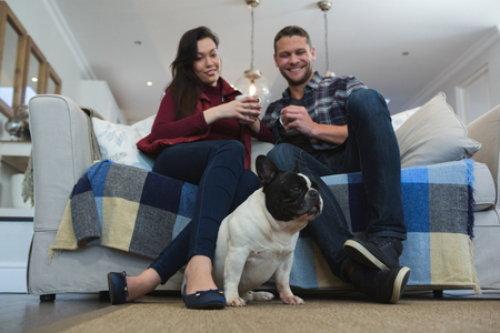 Photo for Couple having coffee with their pet dog in living room at home - Royalty Free Image