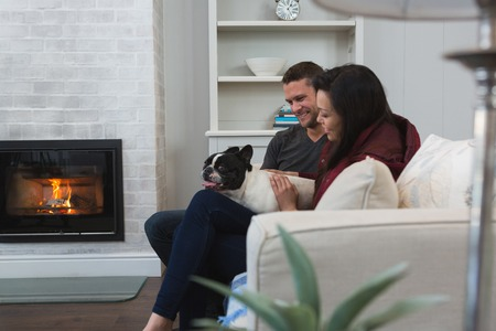 Photo for Couple relaxing with their pet dog in living room - Royalty Free Image