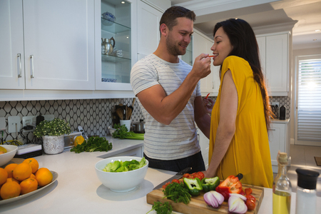 Photo for Man feeding woman in kitchen at home - Royalty Free Image