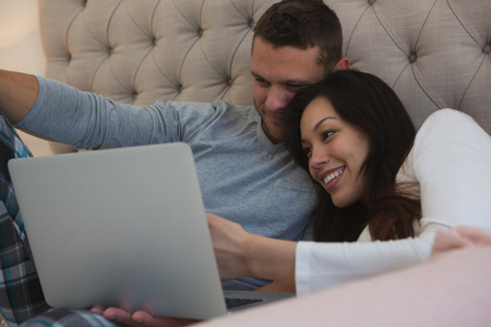 Photo for Couple using laptop in bedroom at home - Royalty Free Image