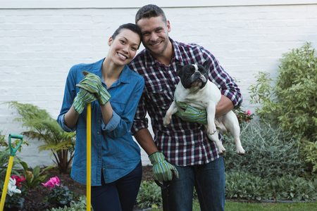 Photo for Portrait of couple with their dog in the garden - Royalty Free Image